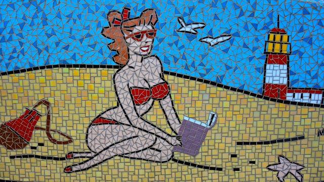 Eine Frau liest am Strand ein Buch