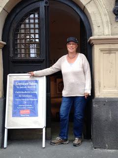 Edna Schuchardt vor Eingang des Ratskellers neben Ankündigungsschild