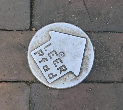 Metallene Markierungen auf dem Straßenpflaster weisen den Weg zur nächsten LEER-Pfad-Station, an der jeweils ein stadtökologisches Thema behandelt wird
